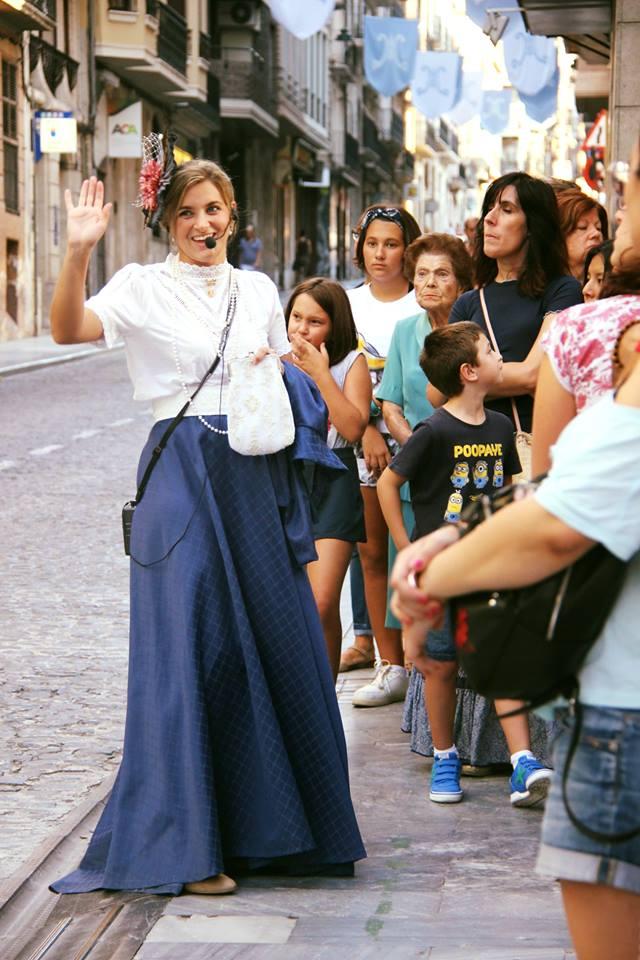 mujer realizando una visita guiada sobre el modernismo, vestida como en la época